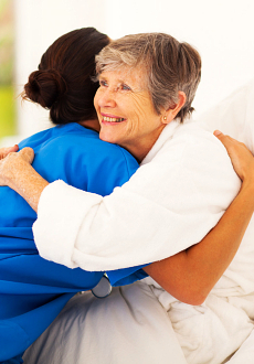 elderly woman hugging her caregiver