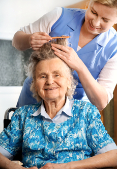 caregiver assisting senior woman in combing hair