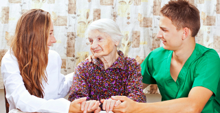 caregivers talking to senior woman