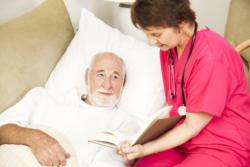 Caregiver is reading some book to the old patient
